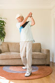 Mature man pretending to play golf