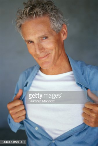 Mature man pulling shirt open, portrait