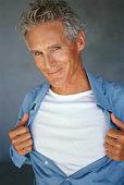 Mature man pulling shirt open, portrait