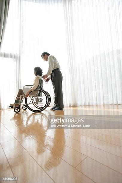 Mature man pushing a woman's wheelchair