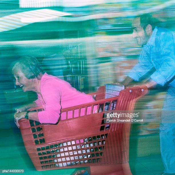 Mature man pushing woman in shopping cart, blurred motion