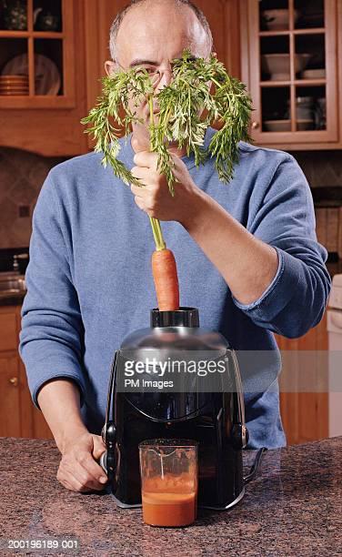 Mature man putting carrot in juicer