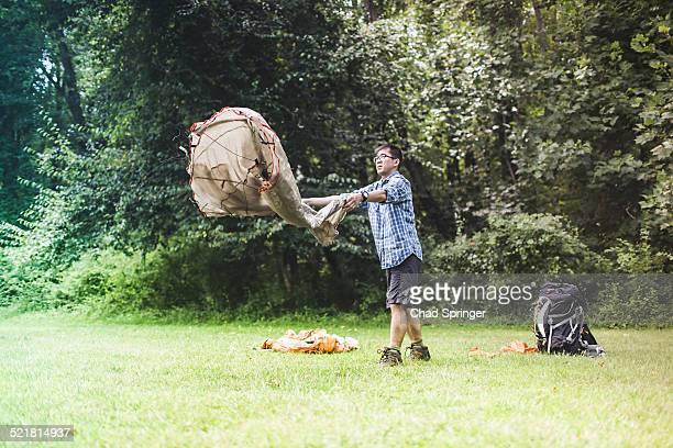Mature man putting up tent