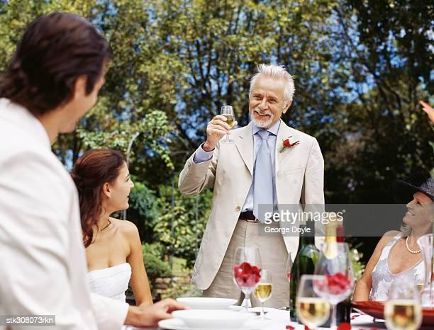mature man raising a toast at a wedding reception