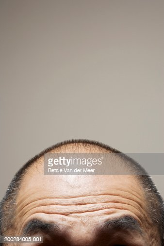 Mature man raising eyebrows, high section, close-up