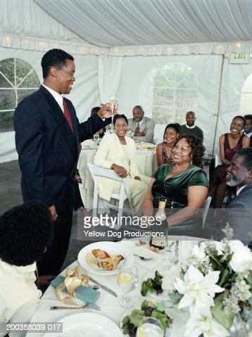 Mature man raising toast to mature couple at celebration : Foto stock