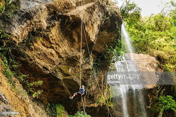 Mature man rappeling next to a waterfall