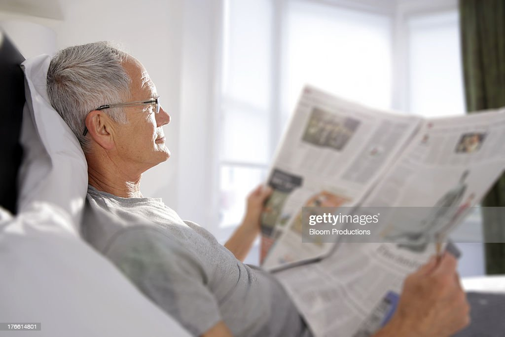 Mature man reading a newspaper in bed : Stock Photo
