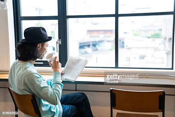 Mature man reading a newspaper in cafe while drinking coffee