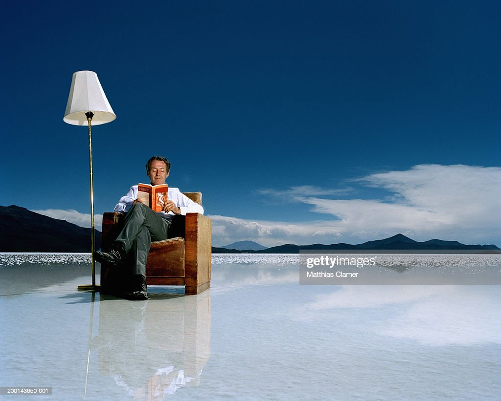 Mature man reading book on salt flat : ストックフォト