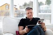 Mature man reading magazine at home