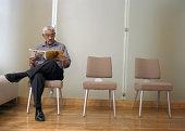 Mature man reading magazine in waiting room
