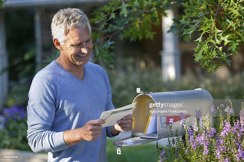 Mature man reading mail at mailbox.