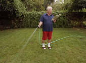 Mature man reading newspaper while watering lawn