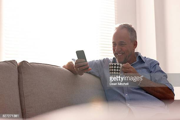 Mature man reading text message while relaxing on sofa