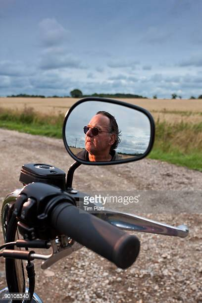 Mature man reflected in motorcycle mirror.