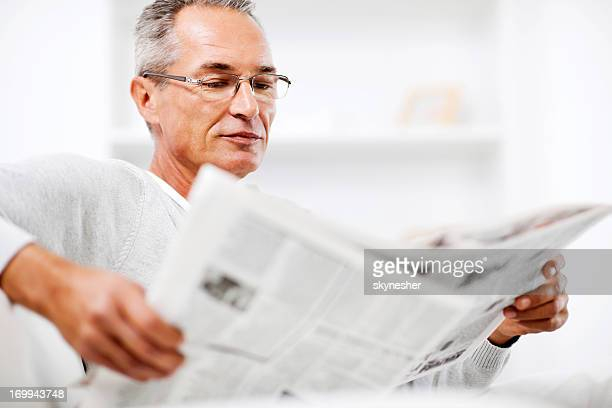 Mature man relaxing at home and reading newspaper.