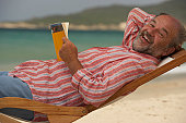 Mature man relaxing in deckchair, holding book, smiling, portrait, close-up