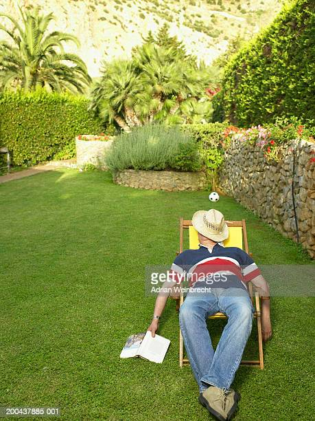 Mature man relaxing in deckchair in garden, hat covering face