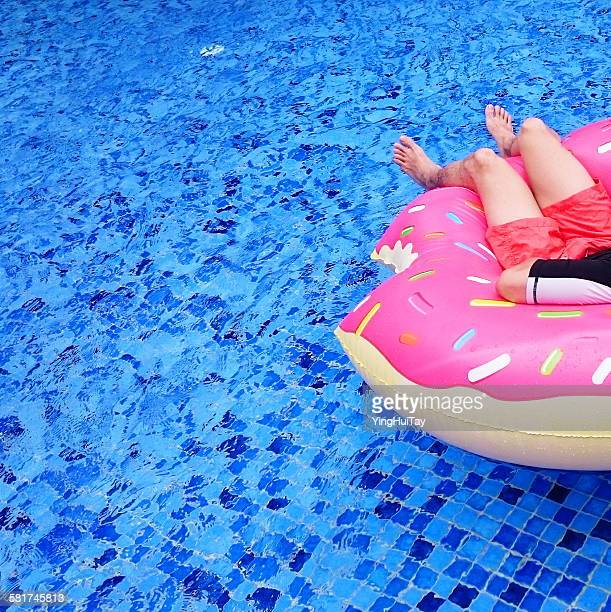 Mature man relaxing on inflatable donut in a swimming pool