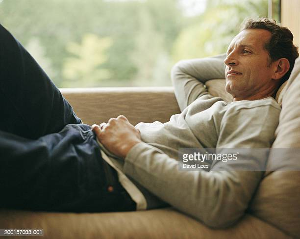Mature man relaxing on sofa, hand behind head