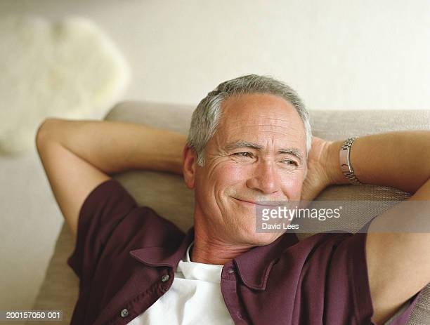 Mature man relaxing with hands behind head, smiling, close-up