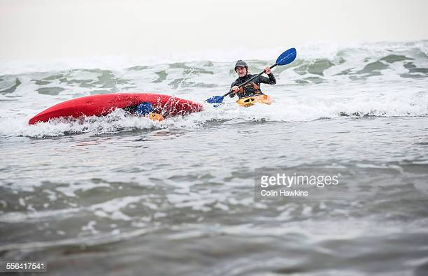 Mature man rescuing person fallen in sea in kayak