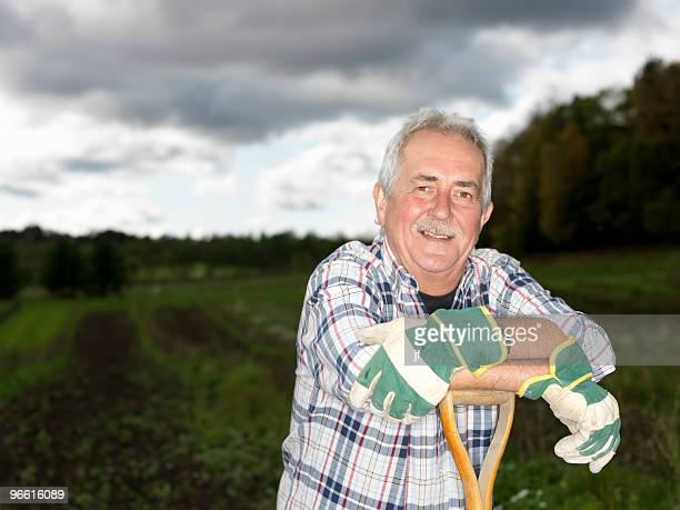 Mature man resting on shovel