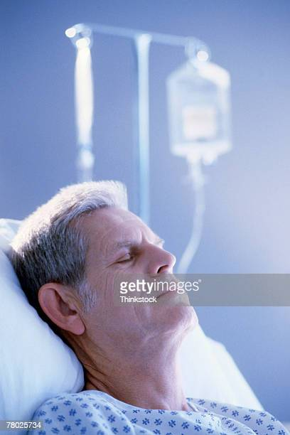 A mature man rests in a hospital bed with an iv bag in the background