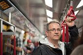 Mature Man Riding Train in Hong Kong