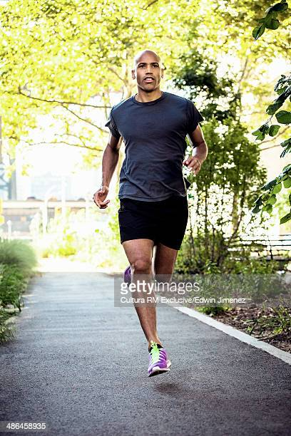 Mature man running along path, New York, USA