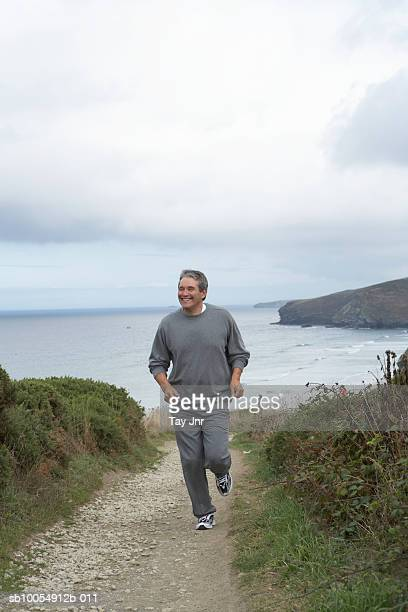 Mature man running along path on bluff overlooking sea, front view