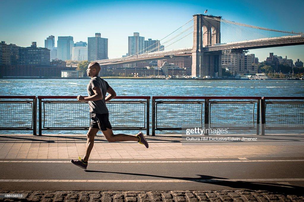 Mature man running along waterfront, New York, USA : Stock Photo