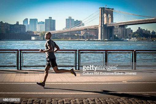 Mature man running along waterfront, New York, USA : Stock Photo