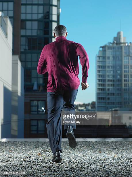 Mature man running on rooftop, rear view