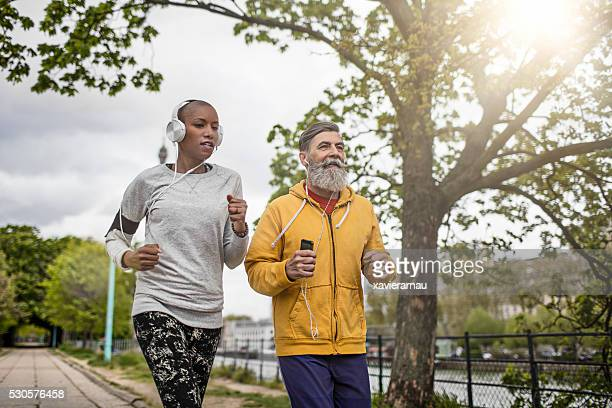 Mature man running with his personal coach in Paris