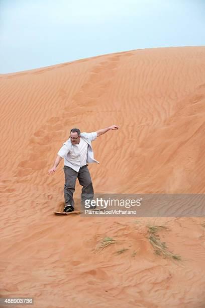 Mature Man Sandboarding on Sand Dune in Dubai Desert, UAE
