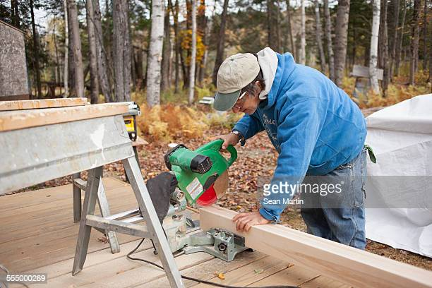 Mature man sawing plank of wood outside house