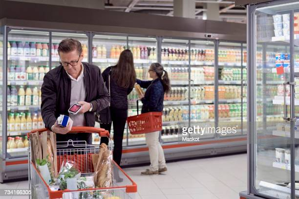 Mature man scanning juice box with reader against women buying at refrigerated section in supermarket