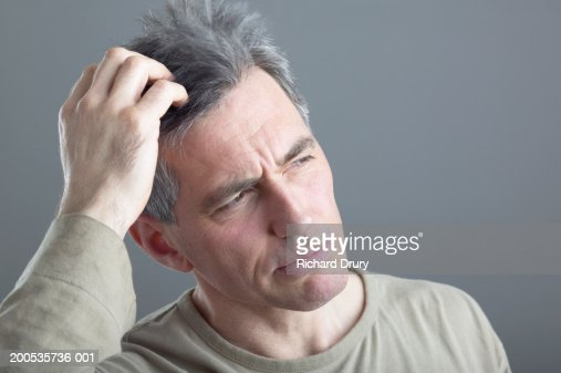 Mature man scratching head, close-up : Stock Photo