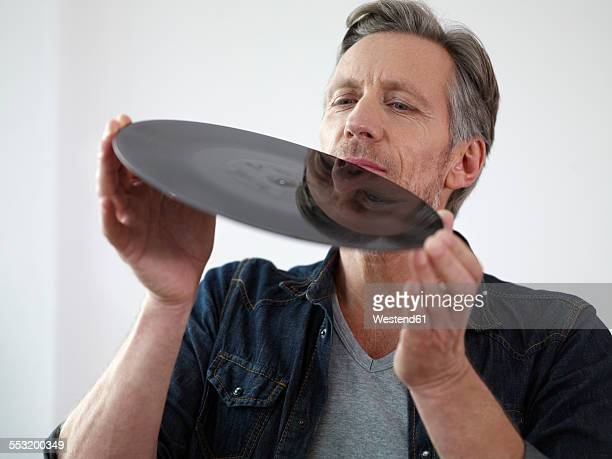 Mature man scrutinizing old vinyl record