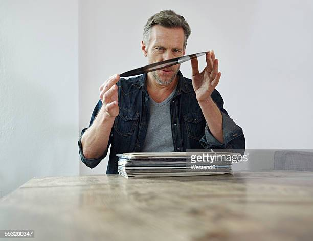 Mature man scrutinizing old vinyl records