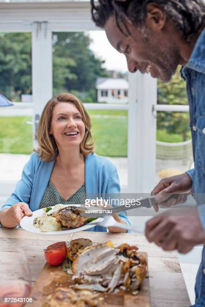 Mature man serving food to friend at dining table