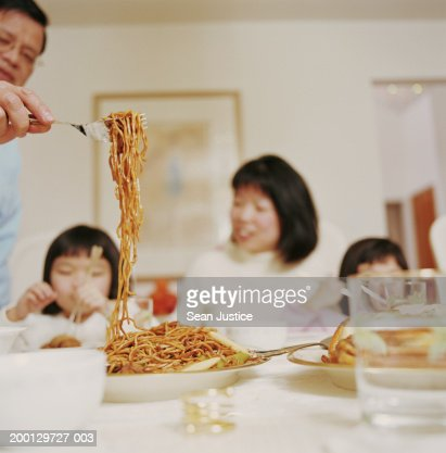 Mature man serving noodles at dinner table (focus on noodles) : Stock Photo