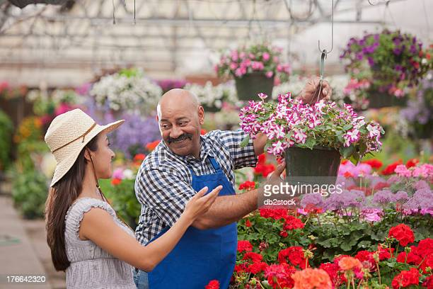 Mature man serving young woman in garden centre, smiling
