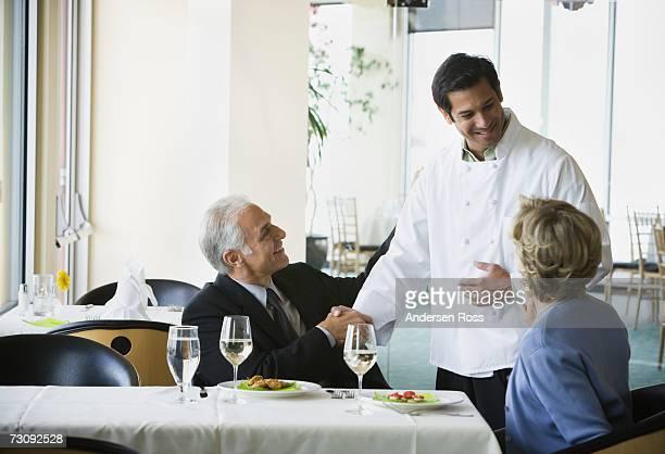 Mature man shaking chef's hand, senior woman watching