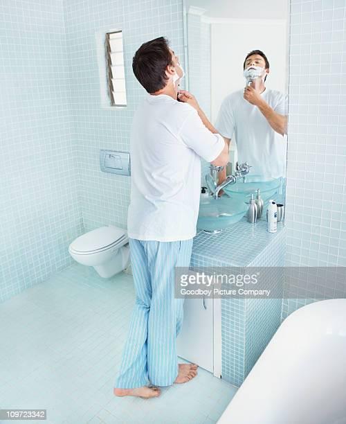 Uomo maturo barba davanti a uno specchio in bagno