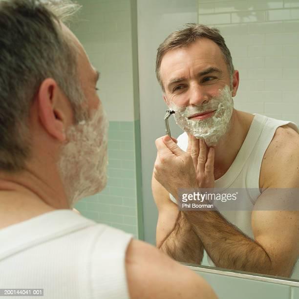 Mature man shaving, reflected in mirror