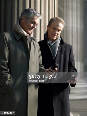 Mature man showing colleague item on phone