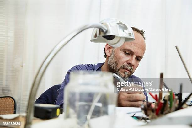 Mature man sitting at desk, writing